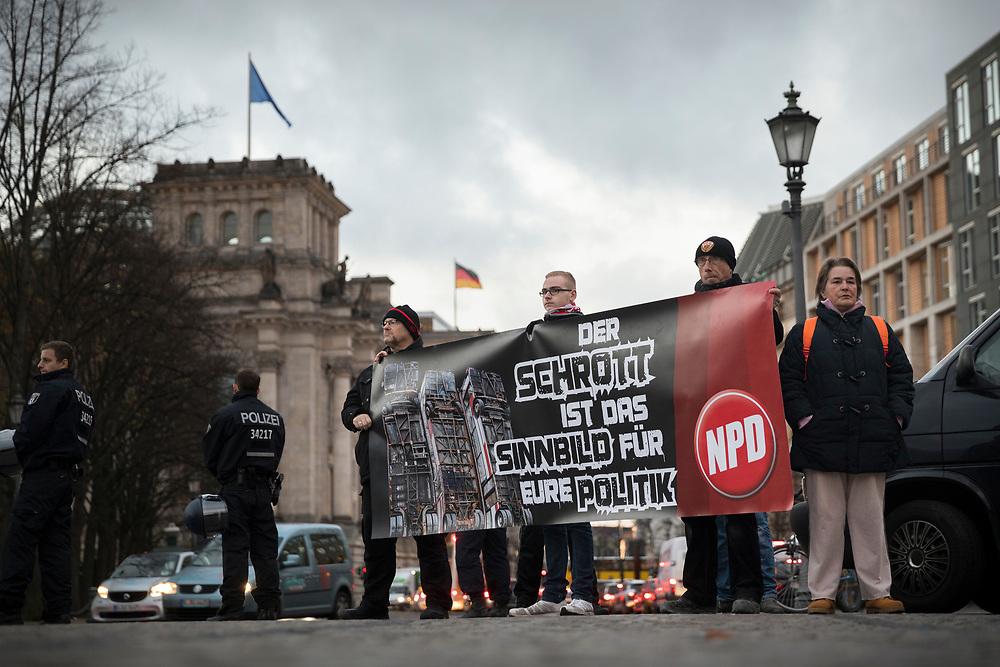 """Etwa ein Dutzend Anhänger der rechtsextremen NPD protestieren in Berlin gegen die Bus-Skulptur """"Monument"""" des syrisch-deutschen Künstlers Manaf Halbouni am Brandenburger Tor. Die drei senkrecht aufgestellten Busse stehen symbolisch für Barrikaden aus Bussen, die 2015 in Aleppo zum Schutz vor Scharfschützen aufgestellt wurden. Demonstranten der NPD mit Banner: Der Schrott ist das Sinnbild für Eure Politik.<br /> <br /> [© Christian Mang - Veroeffentlichung nur gg. Honorar (zzgl. MwSt.), Urhebervermerk und Beleg. Nur für redaktionelle Nutzung - Publication only with licence fee payment, copyright notice and voucher copy. For editorial use only - No model release. No property release. Kontakt: mail@christianmang.com.]"""
