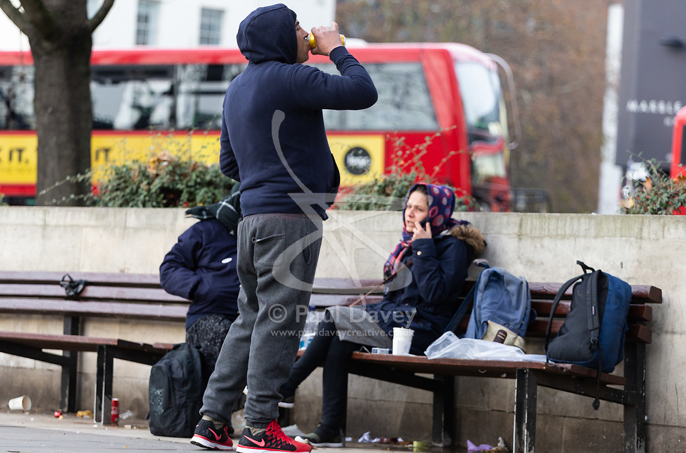 A man swigs from a tin of cider as two women sit on the benches at Marble Arch. Homeless Britons are coming under increasing pressure as a surge of Roma beggars from Romania arrive on the streets of London to take advantage of the generosity of Christmas shoppers. London, December 04 2018.