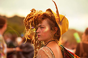 Glastonbury Festival, 2015.<br /> Girl with dreads in hippy boho fashion tribal outfit standing by the stone circle.