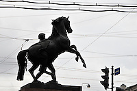 Seen from water level on the Fontanka River, one of the famous Horse Tamer sculptures on the Anichkov Bridge seems hemmed in on all sides by modern life in St. Petersburg, Russia.