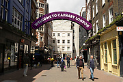 People walk along the famous Carnaby Street W1 on 26th May 2021 in London, United Kingdom. Carnaby Street is a pedestrianised shopping street in Soho in the City of Westminster. Infamous as a street where people would come to parade their fashions in the 1960s, it is home to fashion and lifestyle retailers, including many independent fashion boutiques.