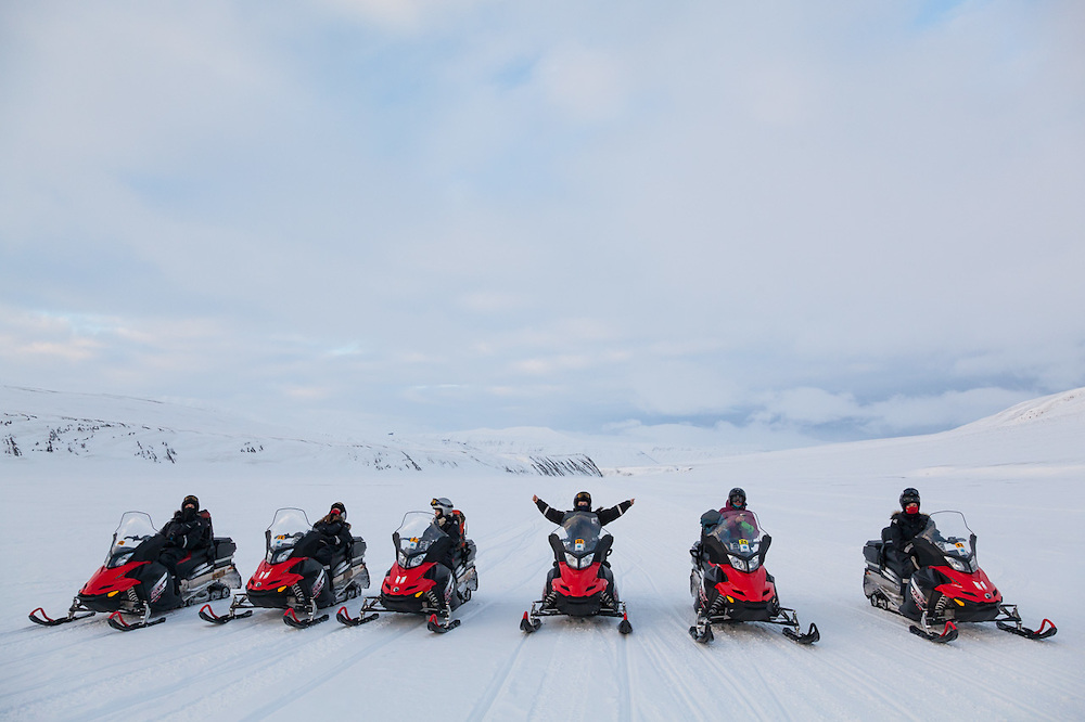 UNIS students wait seated in their snowmobiles in Sassendalen, Svalbard on a class field trip to Tunabreen.