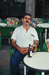 Man sitting at table in cafe with bottle of beer,