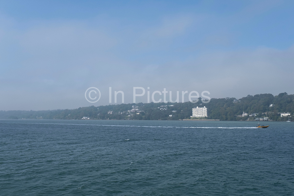 Garth Pier over the Menai Strait on 16th September 2020 in Bangor, Wales, United Kingdom. Garth Pier is a Grade II listed structure in Bangor, Gwynedd, Wales. At 1,500 feet in length, it is the second-longest pier in Wales, and the ninth longest in the British Isles. Designed by J.J. Webster of Westminster, London, the 1,550 feet (470 m) pier has cast iron columns, with the rest of the metal structure made in steel, including the handrails. The wooden deck has a series of octagonal kiosks with roofs, plus street lighting, which lead to a pontoon landing stage for pleasure steamers on the Menai Strait.