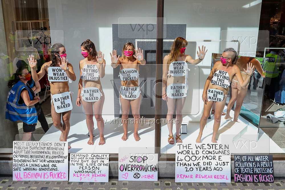 Extinction Rebellion activists have glued themselves to the shop window of H&M in Oxford street in London on Wednesday, Sept 9, 2020. The activists are completely naked, except for strategically placed placards that made a statement about social and environmental injustice in the fashion industry. The signs read 'Fashion is F*cked, Rather Be Naked', 'Won't Wear Injustice, Rather be Naked' and 'Not Buying This Bullshit, Rather Be Naked'. Environmental nonviolent activists group Extinction Rebellion enters its 9th day of continuous ten days protests to disrupt political institutions throughout peaceful actions swarming central London into a standoff, demanding that central government obeys and delivers Climate Emergency bill. (VXP Photo/ Vudi Xhymshiti)