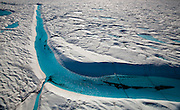 """Blue Melt River, Petermann Glacier, in remote northwestern Greenland, on Nares Strait.  Photographed during a 2009 Greenpeace expedition to investigate the effects of climate change in the Arctic. In 2010 and 2012 Petermann calved ice islands totalling 400 square kilometres. This mage can be licensed via Millennium Images. Contact me for more details, or email mail@milim.com For prints, contact me, or click """"add to cart"""" to some standard print options."""