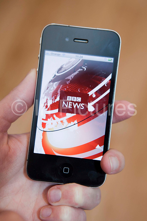 Following BBC news on a i-phone 4, s mart phone connected to the internet.
