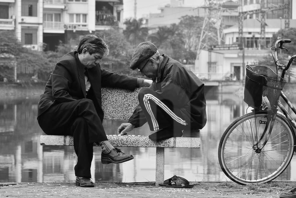Sat on a public bench, two old vietnamese men play chinese chess. Hanoi,Vietnam, Asia