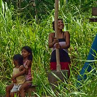 A yanayacu Indian woman and her children pound the hulls off rice in Ayacucho de Tipisha village in Peru's Amazon Jungle.