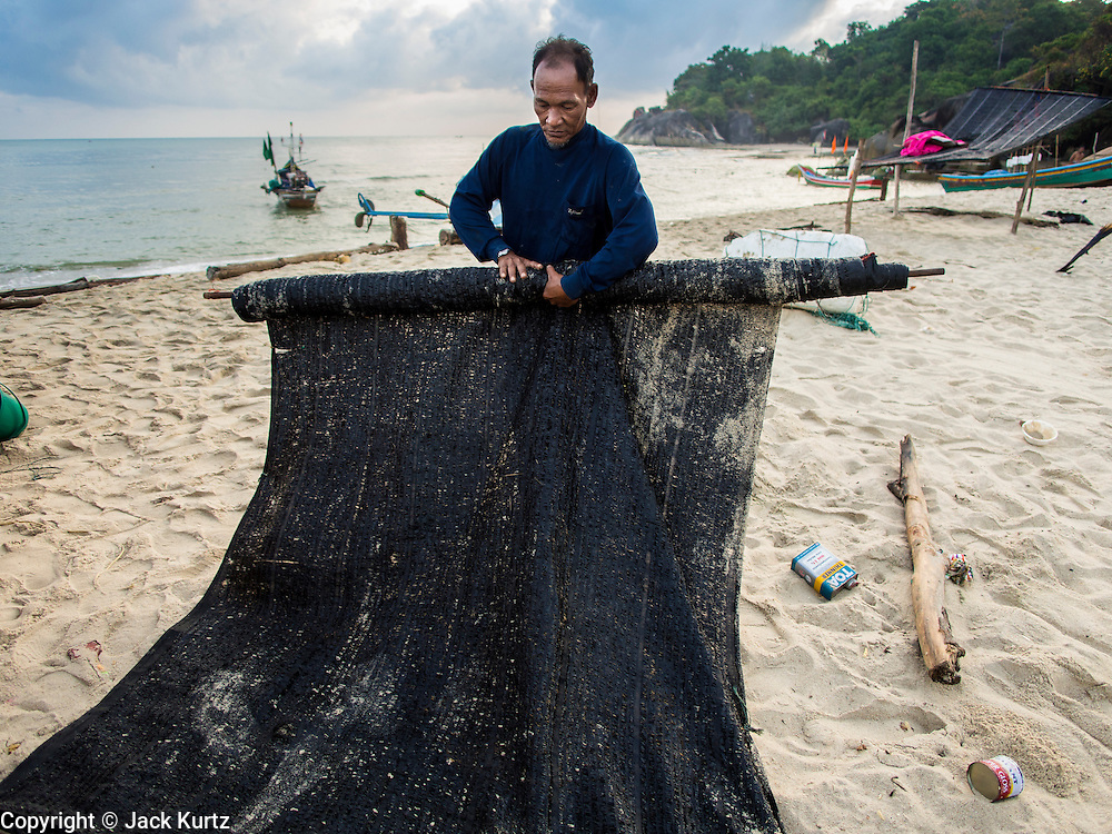 07 FEBRUARY 2014 - KAO SENG, SONGKHLA, THAILAND:  A fisherman rolls up the awning for his boat before putting it in the water in Kao Seng. Kao Seng is a traditional Muslim fishing village on the Gulf of Siam near the town of Songkhla, in the province of Songkhla. In general, their boats go about 4AM and come back in about 9AM. Sometimes the small boats are kept in port because of heavy seas or bad storms.     PHOTO BY JACK KURTZ