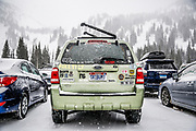 SHOT 3/15/16 9:49:13 AM - A Ford Escape covered with ski stickers and a Skibum1 license plate parked in the lot at Alta ski area. Alta is a ski area in the western United States, located in the town of Alta in the Wasatch Mountains of Utah, in Salt Lake County. With a skiable area of 2,200 acres, Alta's base elevation is 8,530 ft and rises to 10,550 ft for a vertical gain of 2,020 ft. One of the oldest ski resorts in the country, it opened its first lift in early 1939. Alta is known for being very high altitude and receives more snow than most Utah resorts, its average annual snowfall is 514 inches. Alta is one of three remaining ski resorts in America that prohibits snowboarders. (Photo by Marc Piscotty / © 2016)