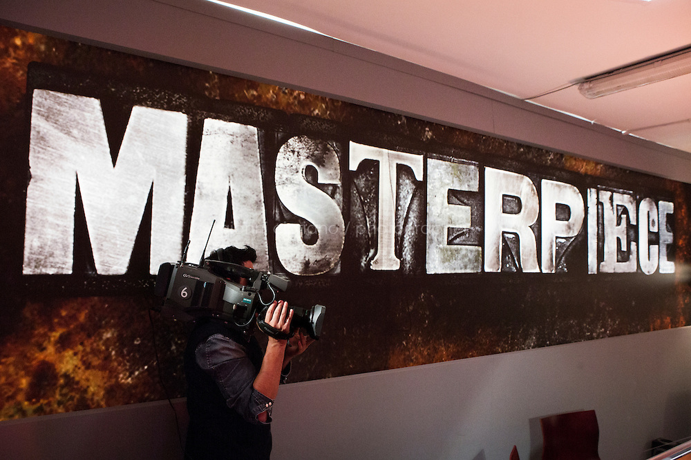 """TURIN, ITALY - 23 October 2013: A cameraman films the jurors of talent show Masterpiece in the juror's room, at the state TV Rai studios in Turin, Italy, on October 23rd 2013.<br /> <br /> Masterpiece is the first talent show for aspiring writers, produced by Rai and FremantleMedia.  The show's objective is to find new talents in Italian literature. 4,919 manuscripts were sent to the program and 80 have been selected for the final selections that will be broadcasted from the Masterpiece studio at the RAI headquarters of Turin starting November 17th on Rai3 national TV. The winner will have his novel co-distributed by RCS and Bompiani, two Italian publishers. <br /> <br /> The jury is composed of Andrea De Carlo (a Milan based author of 17 novels among which is """"Due di due""""), Giancarlo De Cataldo (magistrate, screenwriter and author of """"Romanzo Criminale"""") and Taiye Selasi, author of TBK."""