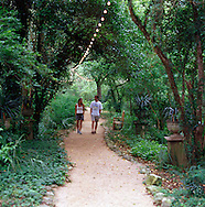 A couple strolls in the evening on the lush grounds of Laguna Gloria, AMOA, Austin, TX
