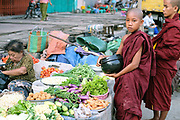 Novice monks collecting alms from the vendors at Mann Thiri market in Mandalay on 26th May 2016 in Myanmar