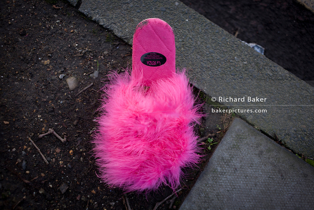 Discarded or forgotten pink slipper in a south London street.
