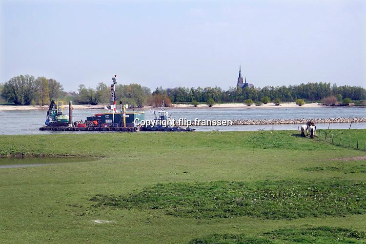 Nederland, the netherlands, Ophemert, 15-4-2019Een dragline is bezig met het positioneren van rotsblokken in de langsdam in de rivier de Waal .Tussen Tiel en Gorinchem zijn kribben in de rivier verlaagd of weggehaald en vervangen door een strook stenen, langsdammen, in de lengterichting van de stroming om zo de waterafvoer bij hoogwater te verbeteren . Het project Kribverlaging Waal is een van de maatregelen van het landelijke hoogwaterveiligheidsprogramma Ruimte voor de Rivier.De Waal is het Nederlandse deel van de Rijn en de belangrijkste vaarroute van en naar Rotterdam en Duitsland . Aftakkingen zijn de minder bevaren Neder Rijn en IJssel.Foto: Flip Franssen