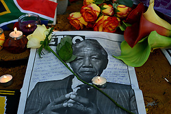 © Licensed to London News Pictures.06/12/2013. London, UK. Flowers and candles left at the statue of Nelson Mandela in Parliament Square, London to pay tribute to late former South African president Nelson Mandela following his death in Johannesburg.Photo credit : Peter Kollanyi/LNP