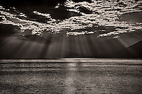 Crepuscular Rays spread over the Olympic Mountain Range and the Hood Canal of Puget Sound Washington state, USA monochrome