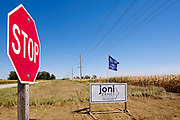 03 SEPTEMBER 2020 - RADCLIFFE, IOWA: A campaign flag for Donald Trump flies over a Joni Ernst campaign sign on the corner of a corn field in central Iowa. Although Iowa's rural economy is struggling because of poor export sales for crops, a loss of about 30% of the corn crop because of a derecho wind storm, and a persistent drought, Donald Trump is still popular with many farmers.         PHOTO BY JACK KURTZ