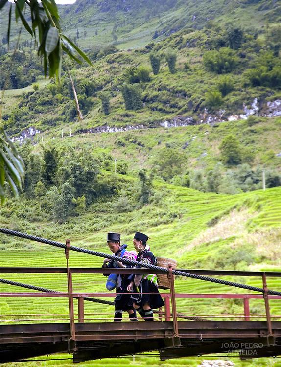 Black Hmong women crossing a bridge in mountains of Northern Vietnam
