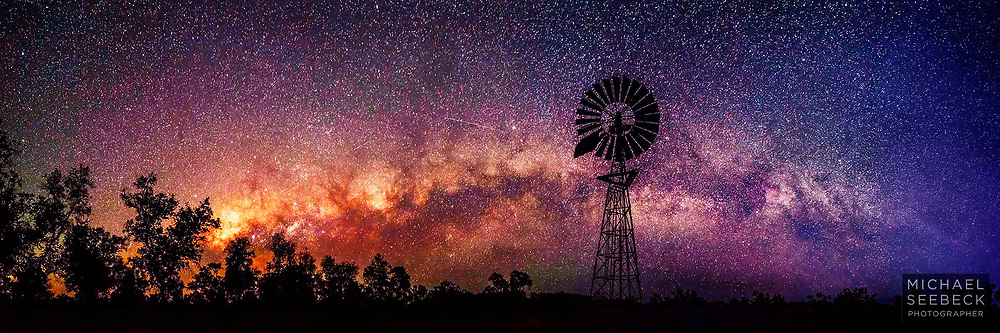 A panoramic photograph of a silhouetted windmill with the setting Milky Way behind, taken just before dawn.<br /> <br /> Open Edition Print