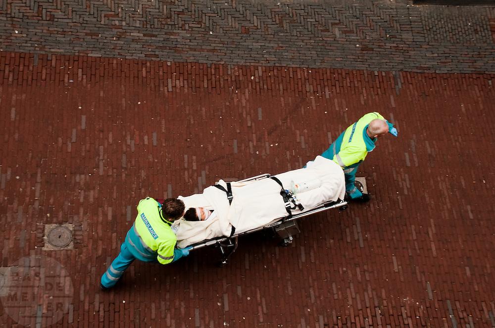 Een slachtoffer van een overval op een schoenenwinkel aan de Lijnmarkt in Utrecht wordt door de ambulancemedewerkers met een brancard afgevoerd