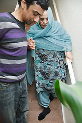 South Asian son helping his mother on stairs .