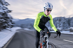 Young cyclist cycling on road wearing protective sportswear