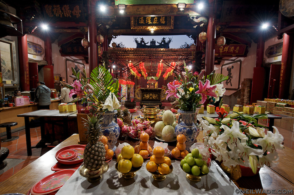 Offerings of fruit and flowers sit before an alter at a Daoist temple in Tainan, Taiwan.