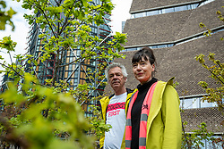 © Licensed to London News Pictures. 04/05/2021. LONDON, UK.  British artists, Heather Ackroyd (R) and Dan Harvey, collectively known as Ackroyd & Harvey, pose with their new work Beuys' Acorns, an installation of 100 oak saplings all grown from acorns, which has opened outside Tate Modern.  The work, begun in 2007, marks 100 years since the birth of Joseph Beuys (1921-86), the hugely influential artist and environmental activist. On show 4 May to 14 November 2021, it is a living sculpture where visitors can reconnect with art from lockdown, rethink their relationship to nature, and reflect on art, activism and the climate emergency.  Photo credit: Stephen Chung/LNP