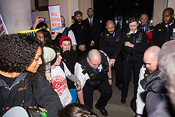 London, UK. 12th February, 2019. A police officer pushes a member of grassroots trade union United Voices of the World protesting outside the Gadson Club in Pall Mall on the occasion of a reception with Justice Secretary David Gauke against his refusal to negotiate with the trade union over their demands for the London Living Wage, annual leave and sick pay for outsourced cleaners, security guards and receptionists working at the Ministry of Justice, all of whom have been on strike for varying periods recently. The Gadson Club is the official alumni club for the Oxford University Conservative Association.