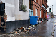 Rubbish from a burnt bin outside the Anchor pub in Digbeth in Birmingham city centre, which is virtually deserted under Coronavirus lockdown on a wet rainy afternoon on 28th April 2020 in Birmingham, England, United Kingdom. Britains second city has been in a state of redevelopment for some years now, but with many outdated architectural remnants still remaining, on a grey day, the urban landscape appears as if frozen in time. Coronavirus or Covid-19 is a new respiratory illness that has not previously been seen in humans. While much or Europe has been placed into lockdown, the UK government has put in place more stringent rules as part of their long term strategy, and in particular social distancing.