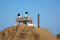 Japanese couple checking cellphones on a park bench overlooking the Pacific Ocean.  Don't want to miss a single text message!