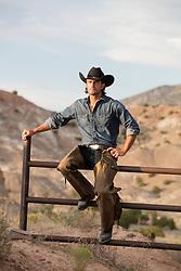 rugged cowboy sitting on a ranch fence