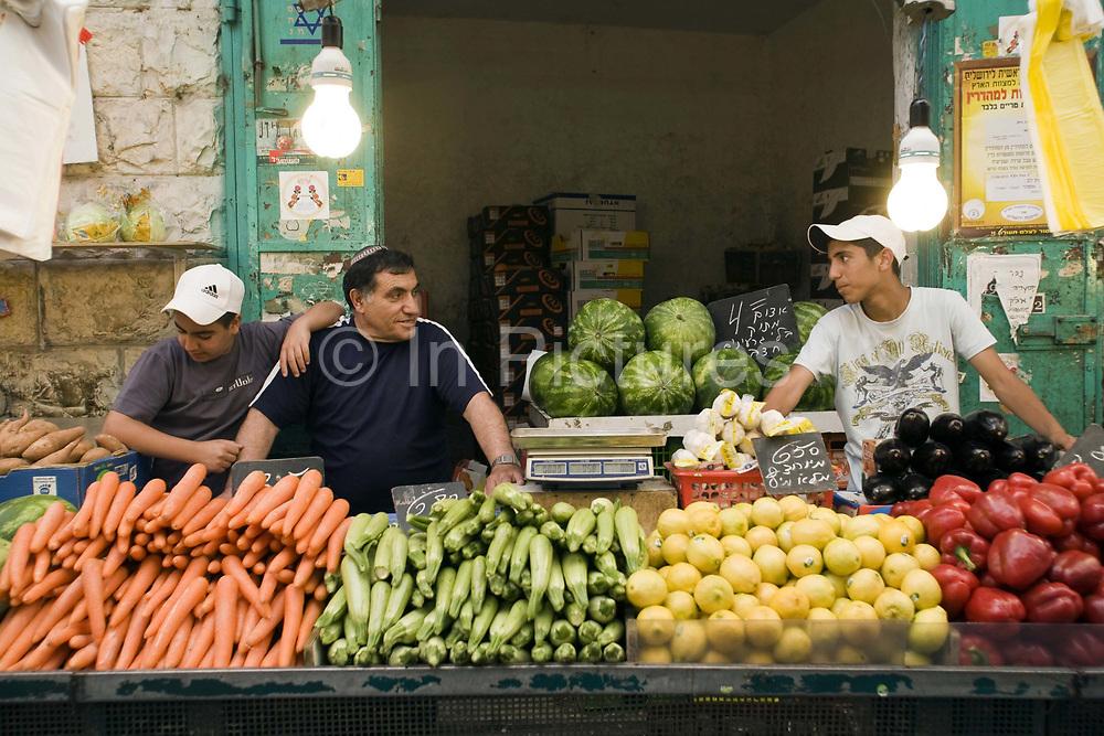 Yidzack and his sons on his vegetable stall at the Mahane Yahuda Market, Jerusalem, Israel