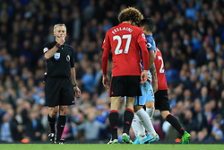 27th April 2017 - Premier League - Manchester City v Manchester United - Referee Martin Atkinson blows his whistle as Sergio Aguero of Man City clashes with Marouane Fellaini of Man Utd - Photo: Simon Stacpoole / Offside.