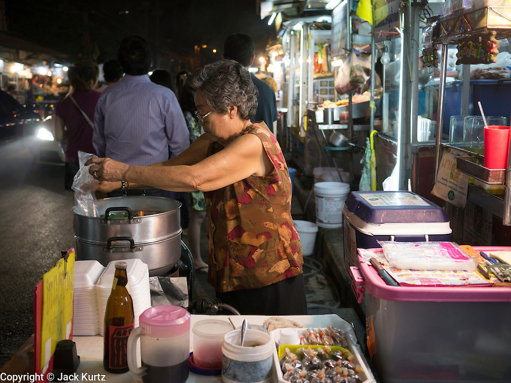 05 JANUARY 2013 - BANGKOK, THAILAND:  A food vendor cooks a meal in her street food stand on Skhumvit Soi 38. Sukhumvit Soi 38, near the Thong Lor BTS Station, is generally considered one of the best street food areas in Bangkok. Most of the food stalls are only open in the evening and they are usually crowded with both Thais and foreign tourists.   PHOTO BY JACK KURTZ