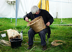 © Licensed to London News Pictures.26/08/15<br /> Egton, UK. <br /> <br /> A basket weaver repairs an old basket at the 126th Egton Show in North Yorkshire. <br /> <br /> Egton is one of the largest village shows in the country and is run by a band of voluntary helpers. <br /> <br /> This year the event featured wrought iron and farrier displays, a farmers market, plus horse, cattle, sheep, goat, ferret, fur and feather classes. There was also bee keeping, produce and handicrafts on display.<br /> <br /> Photo credit : Ian Forsyth/LNP