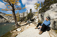 A woman sitting and relaxing next to Perfection Lake, Enchantment Lakes Wilderness Area, Washington Cascades, USA.