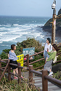 Jeju Island, South Korea - September 12, 2019: Three Chinese tourists visiting Jeju Island in South Korea take turns photographing one another at a viewpoint at Seongsan Ilchulbong, an archetypal tuff cone and national landmark. A security camera is positioned above them.