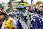 """01 DECEMBER 2013 - BANGKOK, THAILAND: An anti-government protestor with his """"gas mask"""" and """"goggles."""" Thousands of anti-government Thais confronted riot police at Phanitchayakan Intersection, where Rama V and Phitsanoluk Roads intersect, next to Government House (the office of the Prime Minister). Protestors threw rocks, cherry bombs, small explosives and Molotov cocktails at police who responded with waves of tear gas and chemical dispersal weapons. At least four people were killed at a university in suburban Bangkok when gangs of pro-government and anti-government demonstrators clashed. This is the most serious political violence in Thailand since 2010.    PHOTO BY JACK KURTZ"""