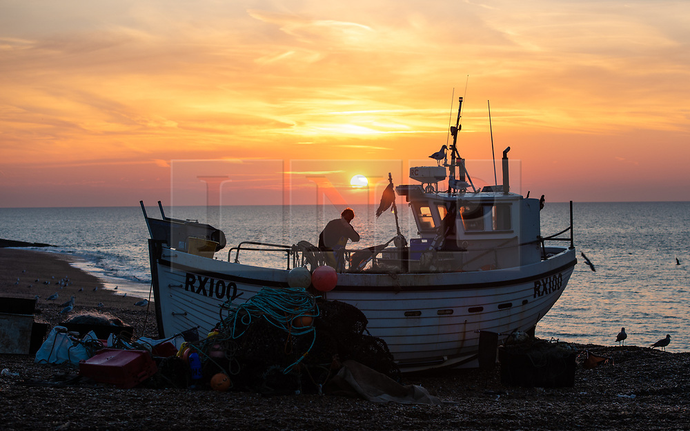 © Licensed to London News Pictures. 16/05/2018. Hastings, UK.  Daybreak over the English Channel, fisherman bring in the morning catch under unseasonably warm conditions. Hastings has one of the last functioning and the largest beach-launched fishing fleet in Europe. Boats intentionally run aground on reinforced keels and are winched up out the water by bulldozer. Photo credit Guilhem Baker/LNP