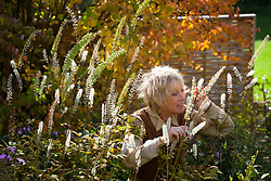 Carol Klein enjoying the scent of Cimicifuga racemosa syn. Actaea racemosa with Cercidyphyllum in the background