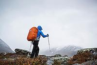 Female hiker in stormy weather in southern end of Tjäktjavagge on Kungsleden trail, Lappland, Sweden