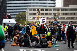 © Licensed to London News Pictures. 07/10/2019. London, UK. Climate change activists stage a sit down demonstration on Westminster Bridge, London, closing the entire bridge to traffic, as part of a wider two week long demonstration to cause disruption in the capital. The activists are calling for the government to acknowledge and act on climate change. Photo credit : Tom Nicholson/LNP
