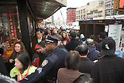 police officer trying to control a mass of people in China Town New York City