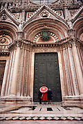 Women with an umbrella looks at the bronze front doors of the Duomo in Siena, Italy.