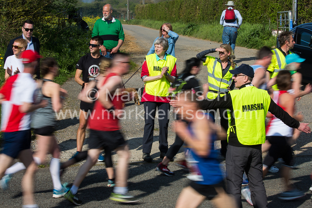 Maidenhead, UK. 19th April, 2019. Prime Minister Theresa May and her husband Philip May act as marshals at the annual Maidenhead Easter 10 charity race on Good Friday.