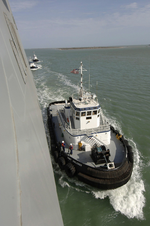 Port Aransas, TX January 15, 2006: Maiden voyage of the USS San Antonio (LPD-17) amphibious transport dock after her commissioning ceremony 14Jan.   Commercial tugboats manuever around the USS San Antonio to bring her into port.  ©Bob Daemmrich /