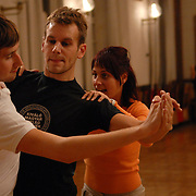 "World Champion same-sex ballroom dancers Robert Tristan Szelei, center, and Gergely Darabos, left, practice their routines with instructor Zilvia Telek, a 4th ranked.Hugarian standard dancer, at a lesson session at Leovey Klara High School in Budapest, Hungary on October 18, 2006, in preparation for the 2nd annual World Championship Same-Sex Ballroom Dancing competition, which was held in Budapest on October 21, 2006. ..This lesson session is one of the few spaces in Budapest which allows same-sex couples to train...Szelei and Darabos, who are known as the ""Black Swans,"" are the reigning world champions in men?s Latin same-sex ballroom dancing. They have been training and preparing to host the 2nd annual World Championship and the Csardas Cup, the first-ever Eastern European same-sex ballroom competition, both held at the Korcsarnok arena.  This is the pinnacle event of the blossoming same-sex ballroom scene...Szelei and Darabos went on to win the men?s Standard division and finished fourth in the Latin division. ..The event was organized by the US-based World Federation of Same-Sex Dancing, which hosted the first World Championship Same-Sex championships in 2005 in Sacramento, California. The Black Swans did a large amount of the coordination and planning in Budapest, a city that had never seen an event of this kind. When government funding fell through, they secured funding from patron Desire (accent on the ?e?) Dubounet, owner of the local Club Bohemian Alibi drag club. ..The World Championship events are newly recognized, but same-sex dancers have been competing on a national and international circuit for a number of years, especially in Europe, including at the Eurogames, the Gay Games, the London Pink Jukebox Trophy and the Berlin Open, among others. Countries including the United States, the Netherlands, Germany and, now, Hungary, hold their own national same-sex championships. Hungary held its first national championships in April 2006...Szelei and Darabos s"